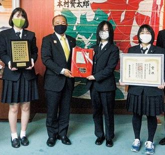 本村市長(中央左)から称讃の楯を受け取る佐賀さん(中央右)と三田さん(右端)、沖津さん(左端)
