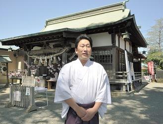 修復工事が実施される拝殿を背にインタビューに答える浅原宮司=4月、氷川神社