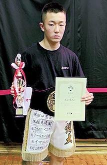 優勝トロフィーと賞状を手にする須田さん