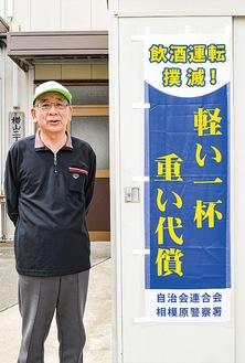 自治会館に掲示したのぼり旗をアピールする竹田会長