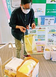 提供された品を引き取るフードコミュニティの中台さん