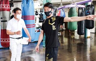 井上さん(左)から指導を受ける中谷選手=3日、M.Tジム