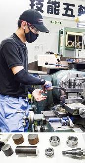 (上)工場の一角にある「技能五輪練習場」で旋盤作業をする工藤さん・(下)左が素材となる丸い金属の棒。右が実際に大会で仕上げた製作物