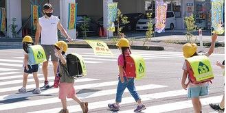 交差点で旗を持つ同スクール足立支配人