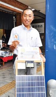 店頭に設置している太陽光パネル発電機を紹介する萩生田会長=19日、淵野辺駅北口