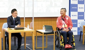 佐藤選手(右)と報告会に登壇した柔道家の野村忠宏さん=同社提供
