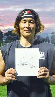 サイン色紙を手に笑顔の石川選手