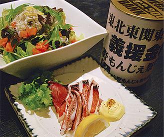 """写真奥のサラダは茨城県産の野菜を中心に作られたもの。なお、手前の「イカの一夜干し」は岩手県の三陸沖から震災前に出荷された品だそう。たまたま市内の市場に入荷し、店主が買い付けた。この店舗ではそのメニューを""""チャリティー""""で提供。会計は募金箱に入れる形をとっている*チャリティーメニューは店舗、日にちにより異なります"""