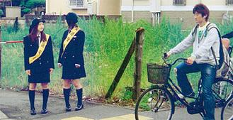 """麻溝台高校(南区北里)の生徒が、貸与された""""警察官の制服""""で交通安全を呼びかける様子"""