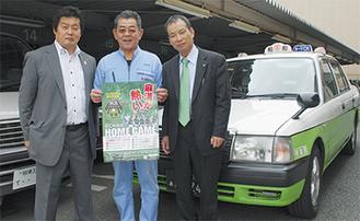 左から久野後援会長、SCポスターをかかげる増田会長、SC後援会長田功事務局長