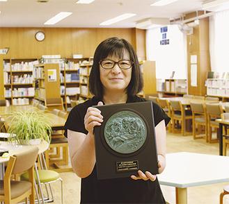 「授業利用で、生徒が自然に図書館になじんできた」と村山教諭。受賞の楯を手に=20日、鵜野森中学校