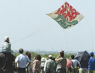 8間凧が空を舞うと観客から歓声が上がった=4日、新戸会場