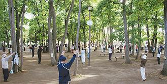 公園いっぱいに広がり体操する=5月10日