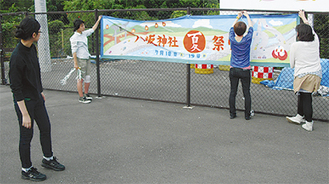 下当麻交差点付近に制作した横断幕を取り付ける学生。19日まで設置