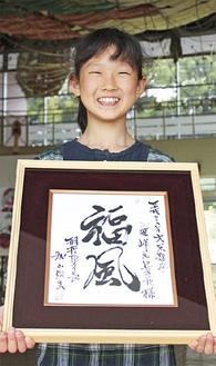 3日の式典で加山俊夫市長から手渡された記念色紙を持って=6日、相模の大凧センター