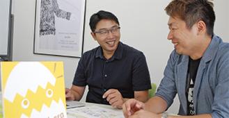 WEB担当の小橋隆司さん(左)と間所さん