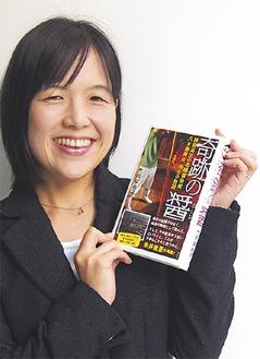 初の著書を手に微笑む竹内さん