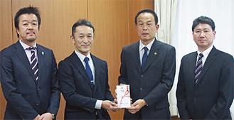 加山市長に寄付金を手渡す実行委員の3人