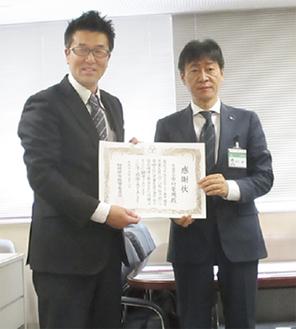 野村教育長から感謝状を受け取る中村社長(左)