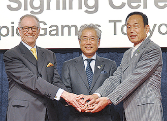 手を取り合う(左から)カルロス・ヌズマンBOC会長、竹田恆和JOC会長、加山俊夫市長