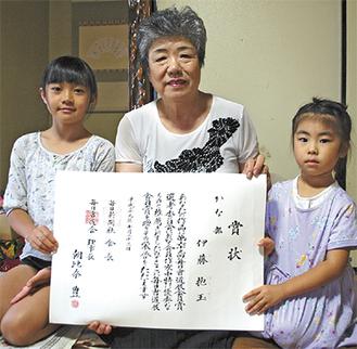 賞状を手にする伊藤さと子さん(中央)と孫の愛莉ちゃん(左)、帆香(ほのか)ちゃん=伊藤さん自宅で