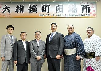 記念撮影を行う後援会役員と相撲協会会員=8日、町田市役所