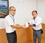 寄付金を手渡す大川会長(右)