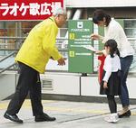 相模大野駅前で反射材を配布する佐藤暁区長=6日
