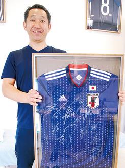 選手からスタッフにプレゼントされたユニフォームを持つ久保田さん=くぼたスポーツ接骨院東林間院にて