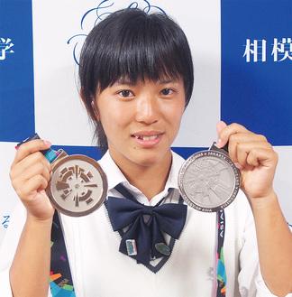 2つのメダルを手にはにかむ伊佐さん=11日 相模女子大学中学部・高等部