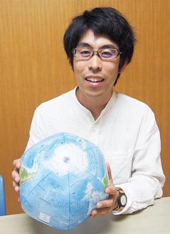 地球儀の南極大陸を示す新井さん