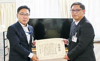 寄贈したテレビの前で感謝状を持つ上島店長(右)と樋口環境共生部長=10月3日
