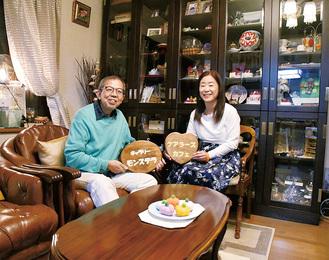 自宅兼ギャラリーで手作りの看板を持つ山田さん夫妻