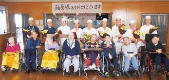 花束を手に笑顔を見せる鮨商の組合員と施設の入居者
