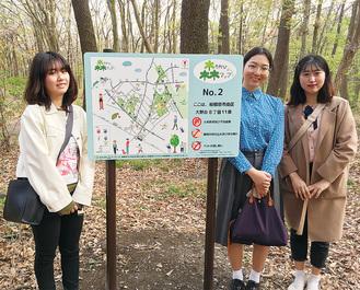 緑地内16カ所に設置された看板を見学に訪れた(左から)半田さん、鴨治さん、ユンさん=6日、木もれびの森