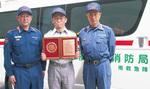 開発に携わった南消防署救急隊員の大田貴広さん(中央)を囲む三澤誠消防司令長(左)横田明文署長(右)