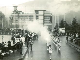 声援を受け、相模湖漕艇場を出発する聖火。先頭が井草さん=1964年10月8日 井草さん提供