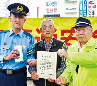運転卒業証書と記念品を片山署長(左)、鈴木会長(右)から受け取る三田さん