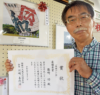 最優秀作品に選ばれた自身の写真「新時代の胎動」を前に、賞状を見せる篠崎さん