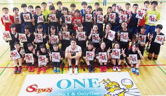 練習後、本間選手(前列中央)を囲みVサインを作る市内選抜の中学生