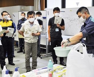 消毒液の作り方について学ぶ担当職員たち =14日、消防指令センター