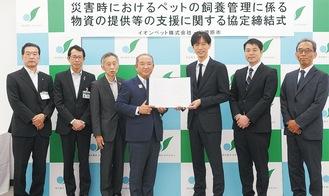 協定書を手にする本村市長(左から4番目)と米津社長(右から3番目)