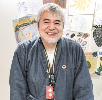 お気に入りの絵を背後に笑顔の齊藤さん