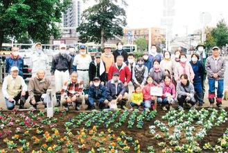 自治会、長寿会、子ども会が協力して花を植えた=7日