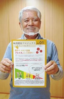 ニュースレターを手に笑顔を見せるプロジェクトメンバーの井上恭男さん