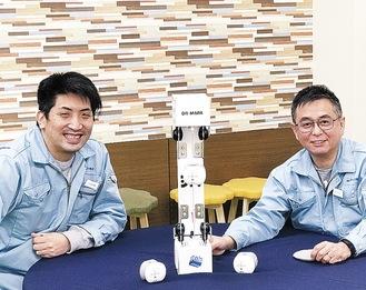 輸液セットに取り付けたDRーMARKを前に笑顔の商品企画グループの相馬さん(右)と同グループの中尾さん