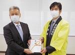 土井校長(左)に目録を贈る金井代表取締役