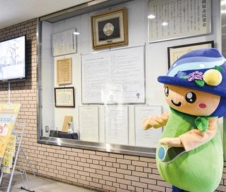 市役所ロビーに掲示されている条例全文を示したパネルと市マスコットキャラクター「さがみん」=20日撮影