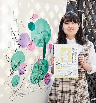 タペストリーの前で講演会のポスターデザインを手にする石井さん