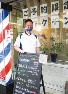 ワタナベ理容室の渡辺晋悟店長。手前の黒板にはワクチン予約情報が書かれている